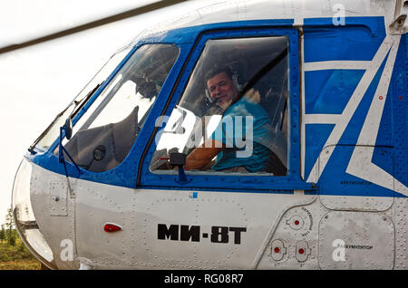 Yamal, Russia - August 2011: Portrait of a pilot of a MI-8T helicopter close-up in a cockpit window. - Stock Photo
