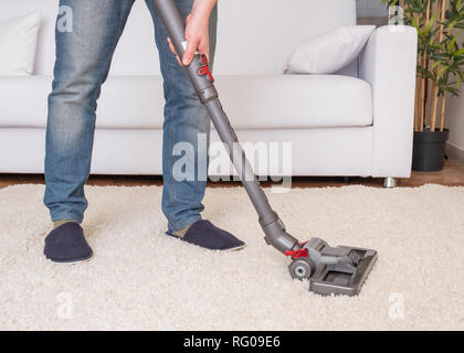 Vacuuming white carpet using the vacuum cleaner - Stock Photo