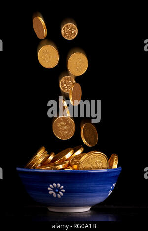 Pot of gold concept with chocolate gold coins falling in to a pot on a black background - Stock Photo