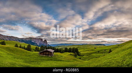 Hilly agricultural countryside with green pastures and a wooden house at Seiser Alm, Alpe di Siusi, the mountain Schlern, Sciliar, in the distance, at - Stock Photo
