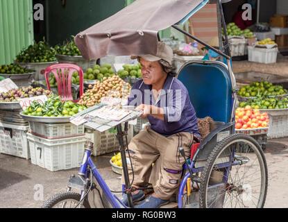 cyclo rickshaw driving rickshaw on street in Hoi An Vietnam - Stock Photo