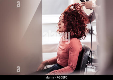 Nice red haired woman having her hair straightened - Stock Photo