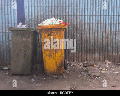 Plastic waste full of garbage bin dirty green and yellow on dirty light blue of wall. - Stock Photo