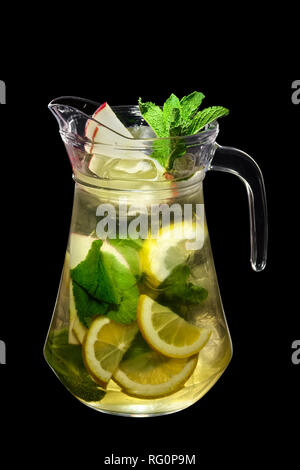 Lemon, apple and mint cold lemonade in pitcher isolated on black background - Stock Photo