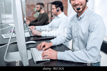 smiling call center operator works on the computer - Stock Photo