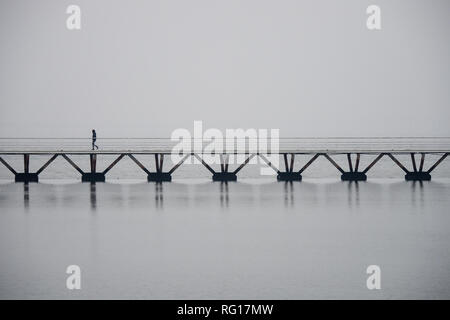 Lonely man walking on a bridge over water in Lisbon, foggy atmosphere, copyspace - Stock Photo