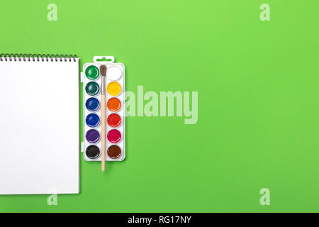 Watercolor paints and brushes with canvas for painting with copyspace on green background