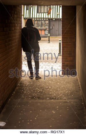 Man leaning on a wall in an alley - Stock Photo