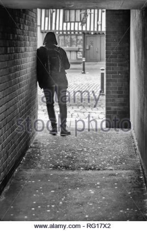 Man leaning on a wall in an alley in black & white - Stock Photo