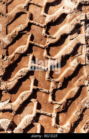 Dried tire mud track printed in construction site soil. - Stock Photo