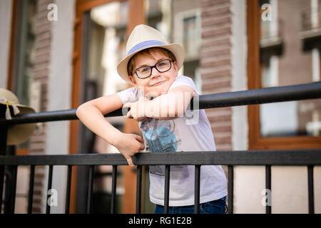 Blonde boy in the straw hat and big glasses staying among beautiful old houses. - Stock Photo