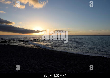 sunset at the rocky beach of Valle Gran Rey, La Gomera, Canary Islands, Spain - Stock Photo