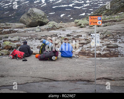 ODA, NORWAY-JUNE 22, 2017: Group of backpack tourists sitting on the top of the mountain on the way to Trolltunga - Stock Photo