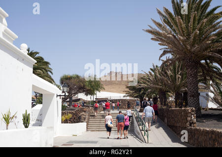 Tourist visiting the town of Teguise with the 16th century castle, Castillo De Santa Barbara on top of the mountain, Canary Island, Lanzarote, Spain - Stock Photo