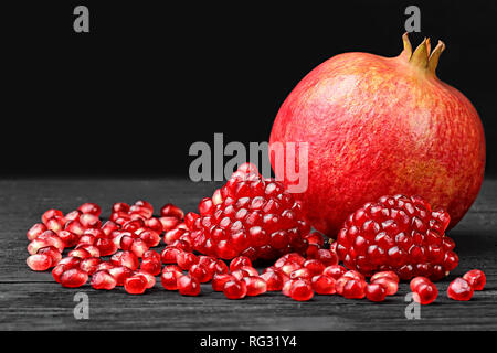 Pomegranate seeds on black wooden table(selective focus). - Stock Photo