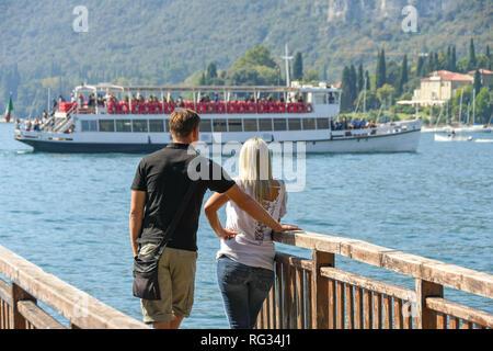 GARDA, LAKE GARDA, ITALY - SEPTEMBER 2018: Two people on a wooden jetty in Garda on Lake Garda looking at a passing ferry. - Stock Photo