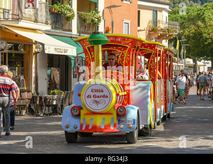 GARDA, ITALY - SEPTEMBER 2018: Tourist land train driving along the promenade in Garda on Lake Garda. - Stock Photo