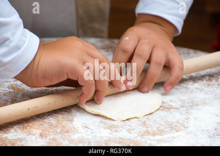 The dough rolling the the child hands. - Stock Photo