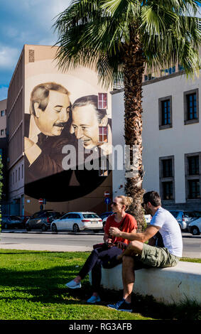 Couple sitting on bench, mural in the background showing famous judges Giovanni Falcone and Paolo Borsellino, Palermo City, Sicily, Italy, Europe - Stock Photo