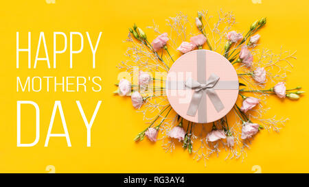 Happy Mother's Day Background. Bright Yellow and Pastel Pink Colored Mother Day Background. Flat lay greeting card with beautiful gift box and pink li - Stock Photo