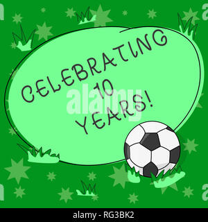 Writing note showing Celebrating 10 Years. Business photo showcasing Commemorating a special day Decennial anniversary Soccer Ball on the Grass and Bl - Stock Photo