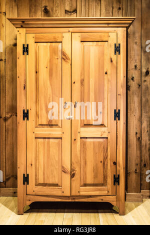 Lovely wooden wardrobe cabin against wood panel wall - Stock Photo