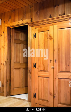 Interior of room with doors and wood paneling inside a beautiful wooden cabin - Stock Photo