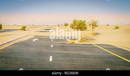Sand is taking over a desert road near Dubai in UAE. - Stock Photo