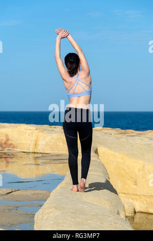 back view of a woman doing a side body stretch outside by the sea wearing a sports bra and leggings - Stock Photo