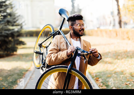 Bearded indian man carrying bicycle on shoulder in the city - Stock Photo