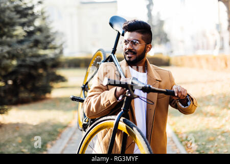 Young asian cheerful businessman holding bike on shoulder in outdoor city. Happy success business man cycling go to work with bike in city - Stock Photo