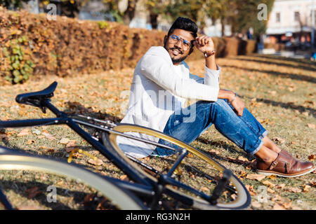 Portrait of bearded indian man resting at park, sitting on grass near the bicycle, looking at camera. Leisure concept. - Stock Photo