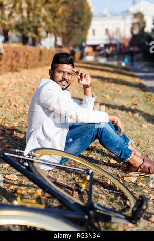 Portrait of bearded indian man resting at park sitting on grass near the bicycle, looking at camera. - Stock Photo