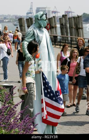 USA, United States of America, New York City: Battery Park, Tourists take pictures with a person dressed like the statue of - Stock Photo