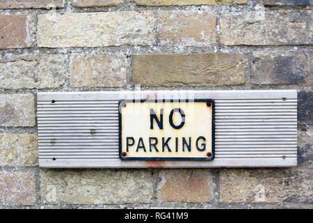 weathered no parking sign on wooden plank, screwed onto brick wall - Stock Photo