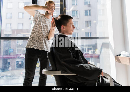 Handsome man at the hairdresser getting a new haircut - Stock Photo