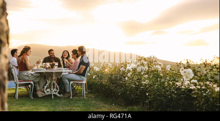 Group of young friends hanging out with drinks at outdoors dinner party. Young men and women sitting around a table having food and drinks. - Stock Photo