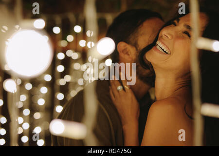 Happy young couple embracing with lights around at party. Young man and woman embracing and laughing.