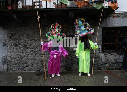 Two participants dressed in traditional clothes and wearing large hats decorated with ribbons and feathers, known as ''Ttutturo' are seen during the Carnival of the Pyrenees villages of Leitza, northern Spain. Carnival parade held in Leitza, a small town located in the north of Navarra, Ancestral costumes from more than a hundred years ago are mixed between defaces of Donald Trump, Mariano Rajoy and even Kim Jong-un himself. - Stock Photo
