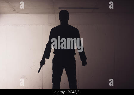 silhouette of an armed man holding his gun and pointing with his laser beam at a target. - Stock Photo