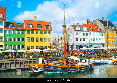 Scenic Nyhavn view with boats by embankment in bright sunshine, people walking and sitting in restaurants, Copenhagen, Denmark