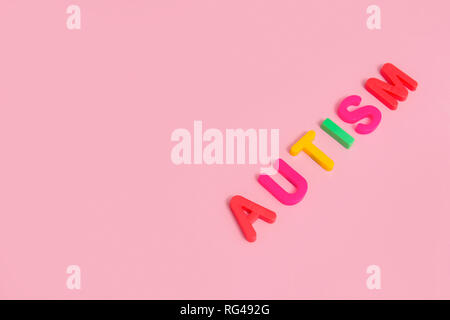 Word AUTISM on pink background, top view - Stock Photo