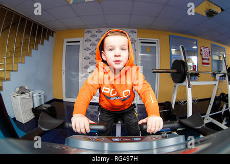 January 29, 2017. Ukraine, Kiev. Subject child goes sports. Caucasian baby 3 years doing cardio training, warming up muscles on bicycle simulator in g - Stock Photo