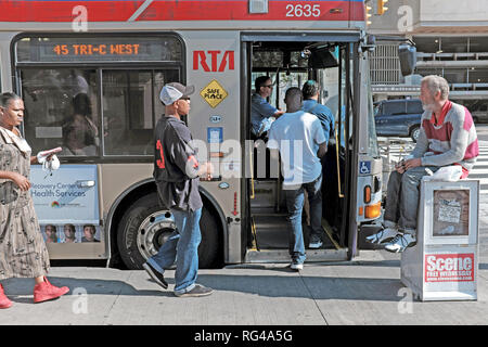 People board a public RTA bus in downtown Cleveland, Ohio, USA during the summer. - Stock Photo