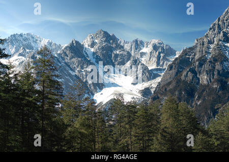 Jade dragon snow mountain situated in Yulong, Yunnan China. The snow covered mountain with rocky peaks with trees in the foreground giving a dramatic - Stock Photo