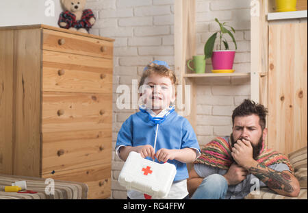 Father and son playing doctor, medicine and treatment concept. Family physician visiting patient at home. Bearded man in colorful scarf with coughing - Stock Photo