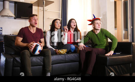 Four young friends sitting on the sofa and watching football match wearing Russian attributes - Stock Photo