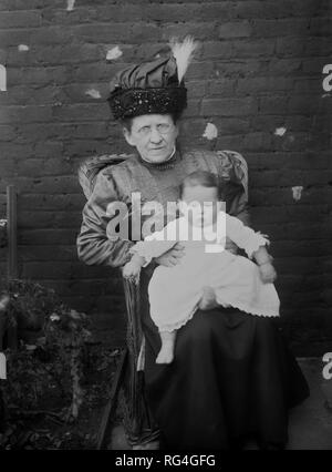 Older Edwardian lady sitting in a wicker chair in a backyard with a small baby on her knee, circa 1910. - Stock Photo