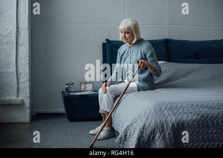 lonely pensive senior woman sitting on bed with walking stick at home - Stock Photo