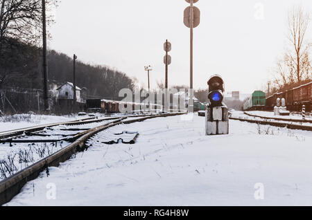 Vintage railway traffic light on old snow covered railway station. Trains, rails, travel, abandoned. - Stock Photo